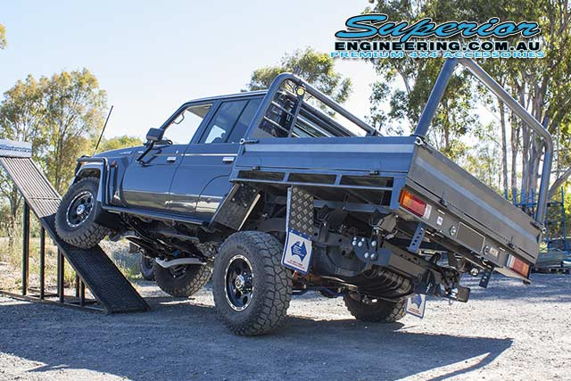 Rear left end view of the 79 Series Toyota Landcruiser with the front left wheel flexed up on the flex ramp