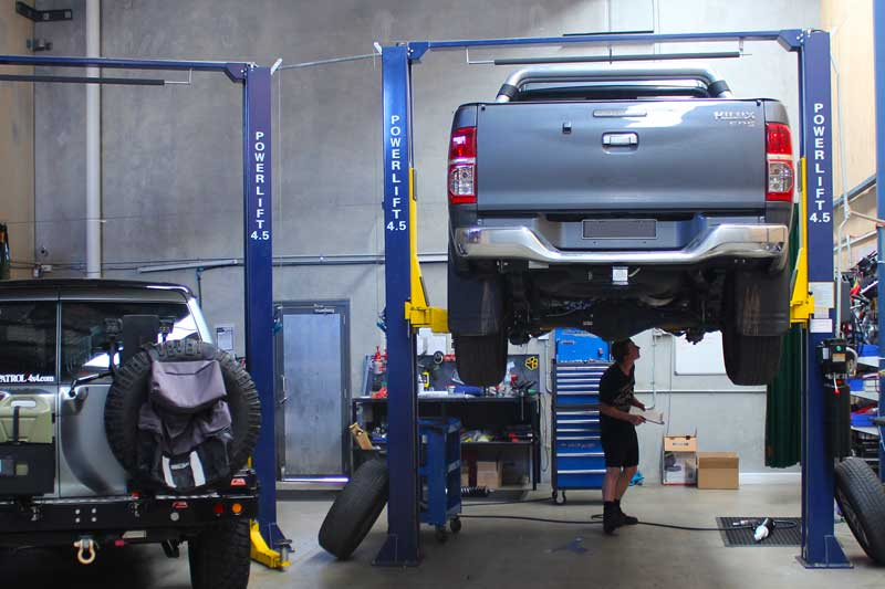 A Hilux on the hoist at Deception Bay workshop with the fitter inspecting the suspension