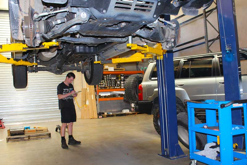 A vehicle fitter inspecting the suspension system of a 4x4 on the hoist at Superior Engineering