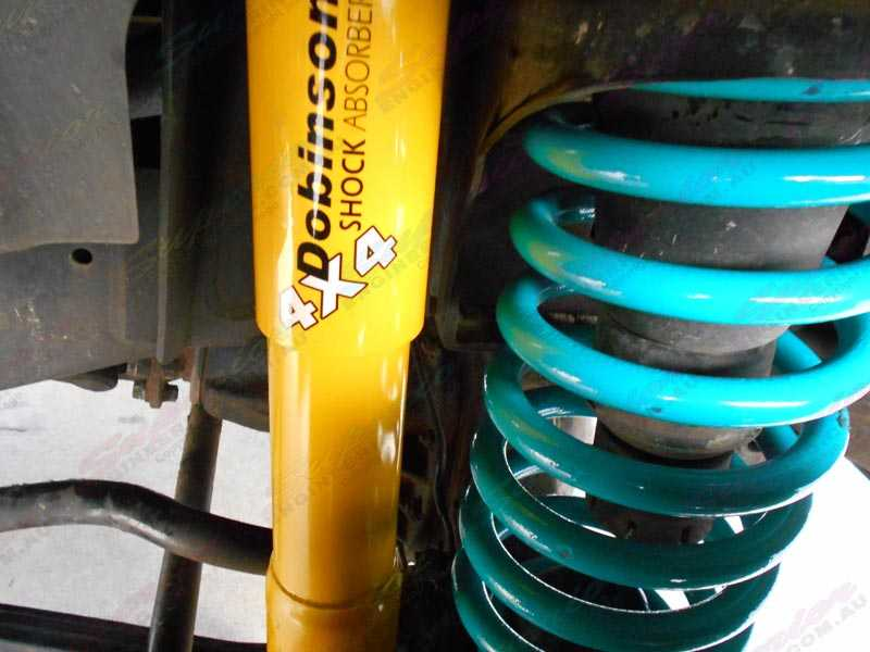 A closeup view of some yellow Dobinson 4x4 shocks and light blue heavy duty coil springs