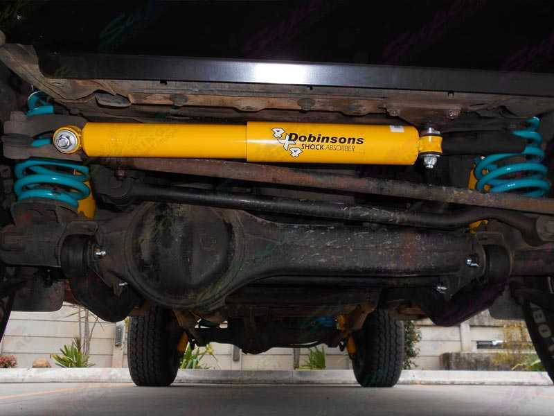Closeup view of a Dobinson 4x4 Steering Damper mounted to the underside of the 105 Series Landcruiser