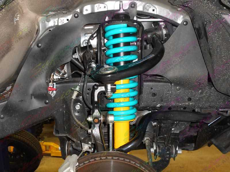Closeup View Of A Yellow And Black Dobinson Shock Absorber And Coil Spring Mounted In The